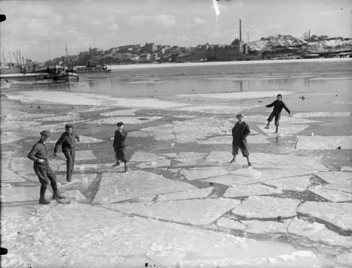 Pojkar jumpar på isflak vid Norr Mälarstrand. I fonden Söderm